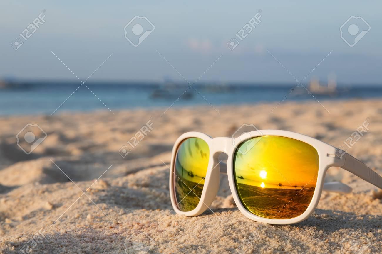 Banque d images - Lever de soleil sur une plage tropicale reflète dans une  paire de lunettes de soleil a0da96d5939f