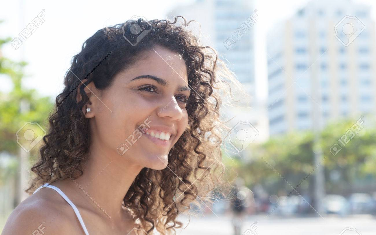 Laughing latin woman outside in a city of latin america with modern buildings and trees in the background - 43010433