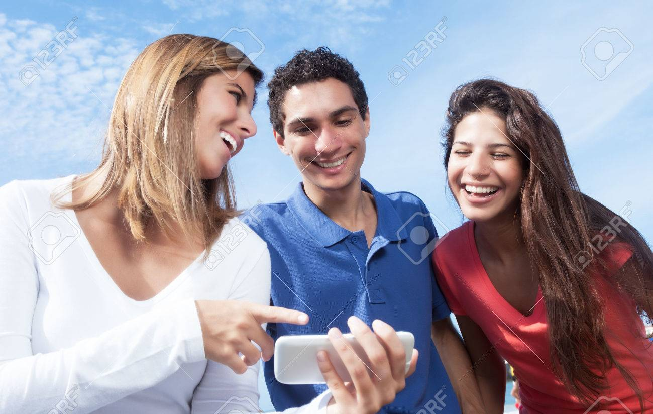 Group of young people showing at pictures on smartphone - 44974698