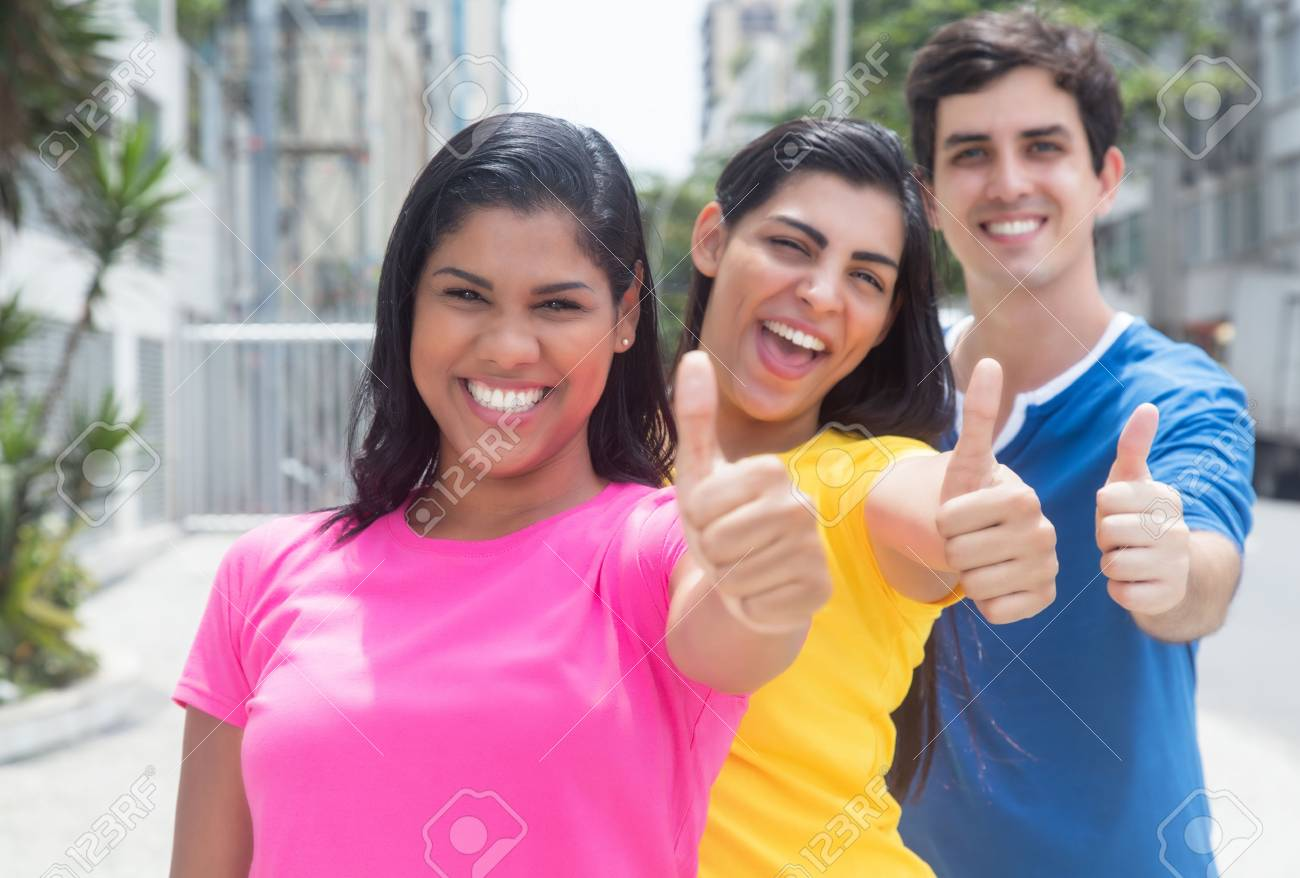 Group of three young people in colorful shirts standing in line and showing thumbs - 49636049