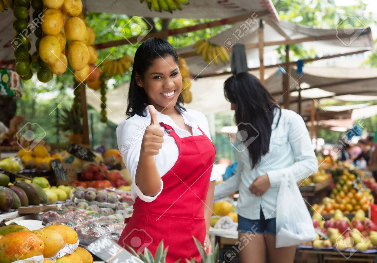 Laughing mexican saleswoman showing thumb on a farmers market - 52059069