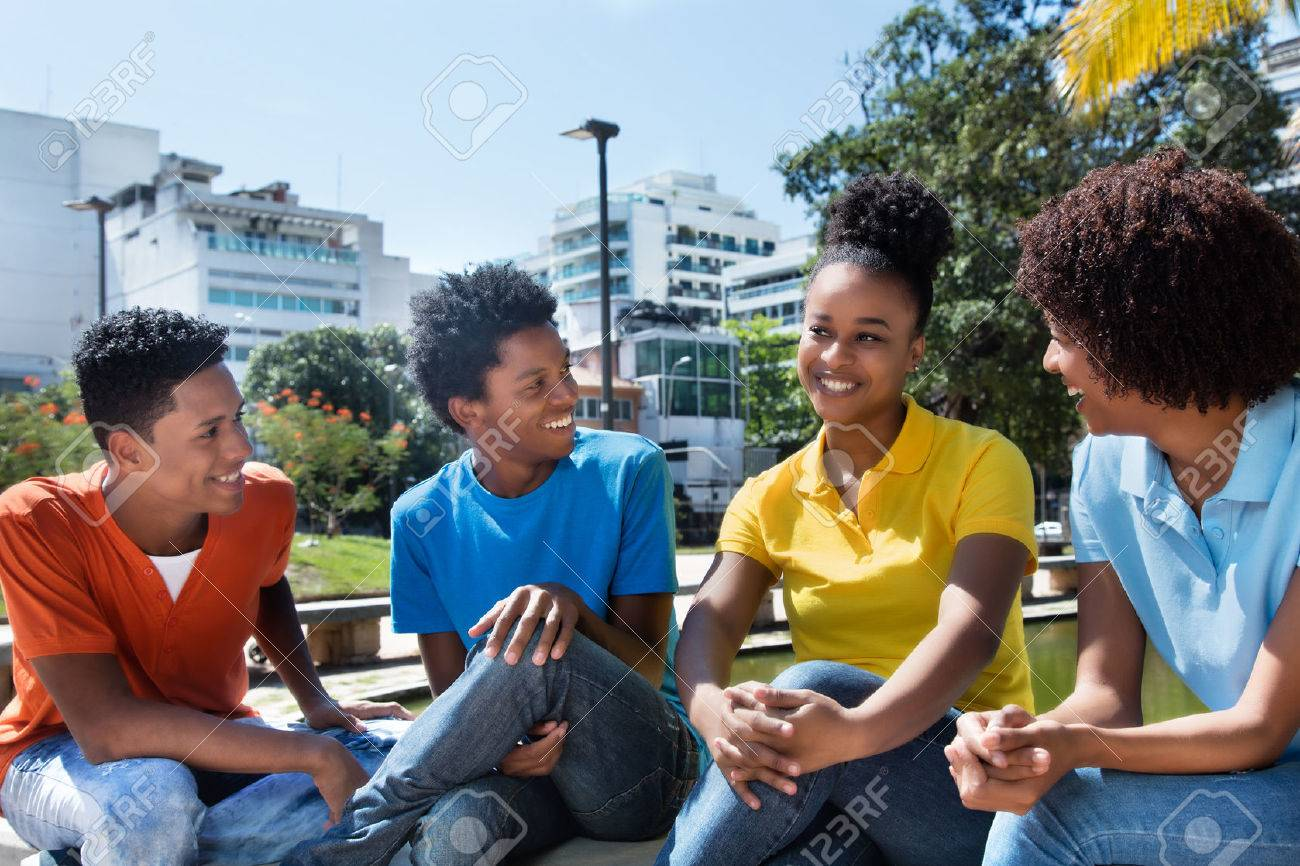 Group of four speaking latin american young adult outdoor - 63534696