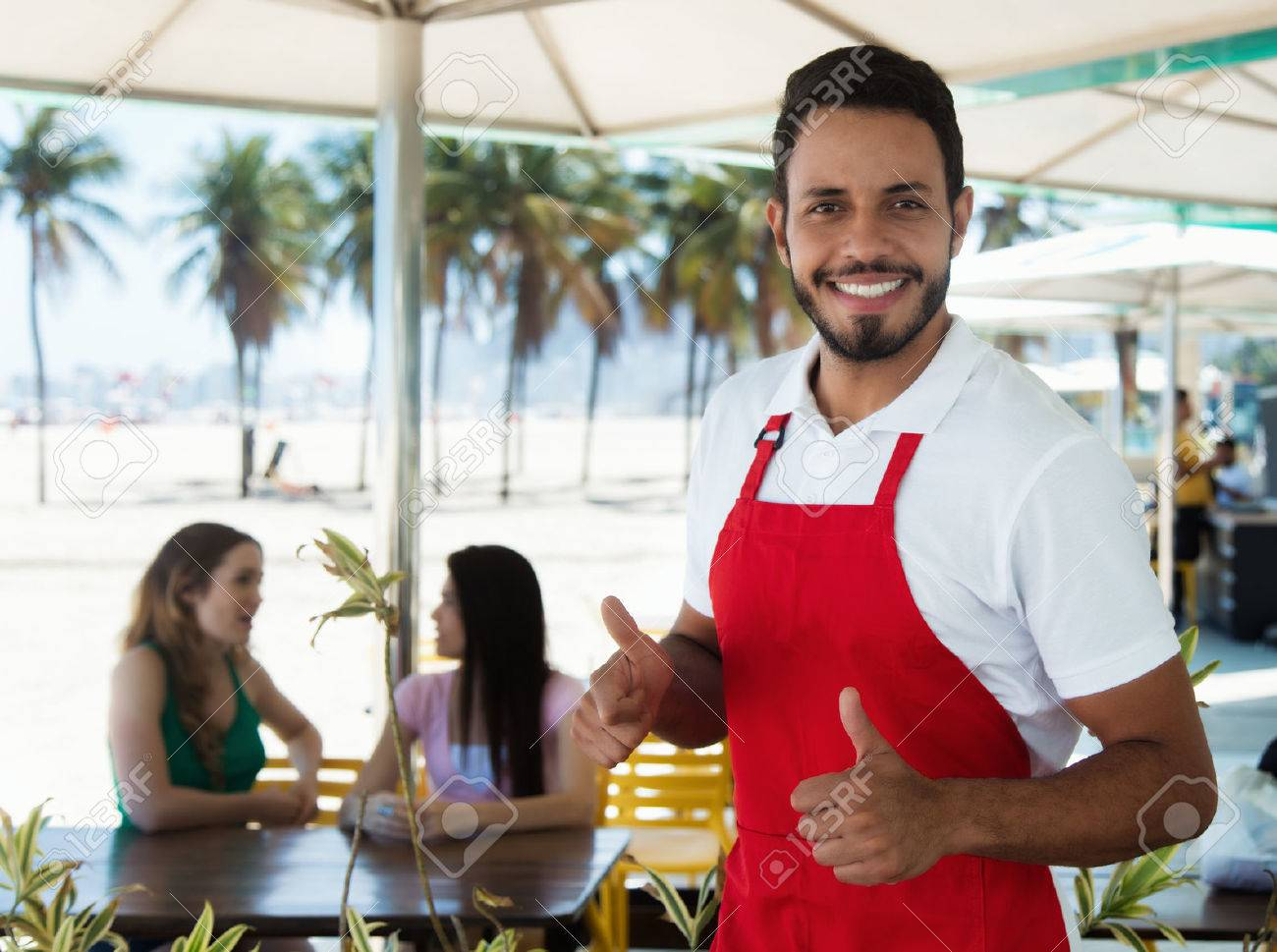 Laughing waiter of a cocktail bar at beach - 67418269
