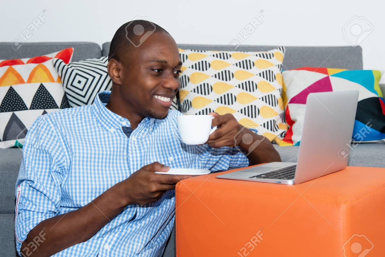 African american man watching movie clip online with laptop - 105799329