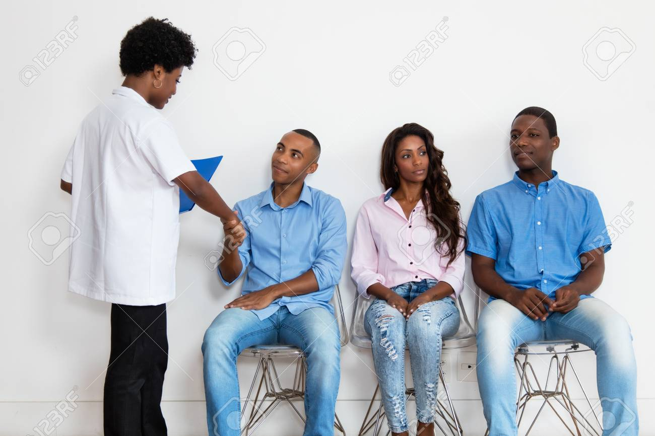 African american nurse with patients at waiting room - 107680958