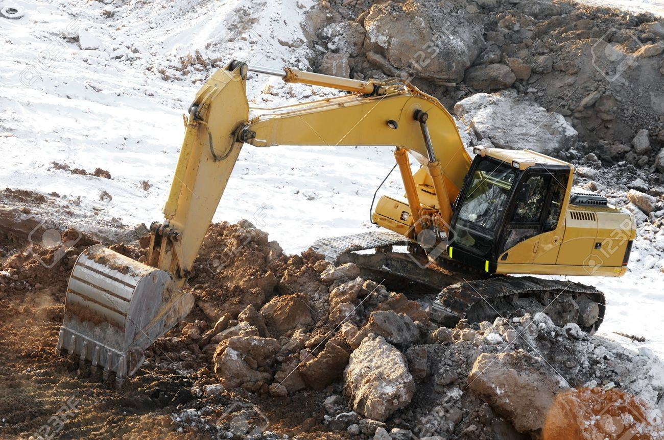 Yellow excavator loader at construction site excavating earth with bucket in winter Stock Photo - 6419163