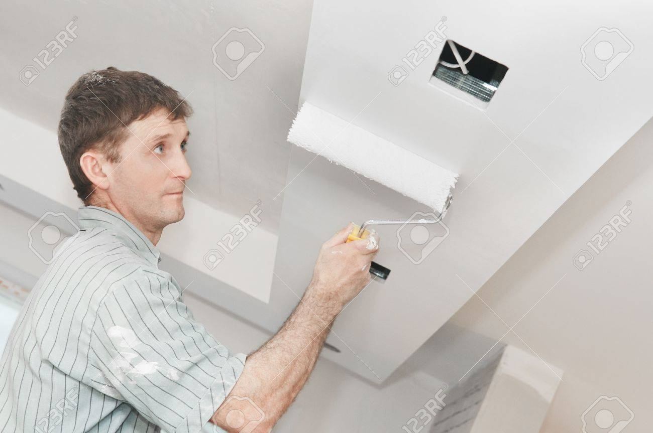 Painter worker at decoration work painting a ceiling with roller Stock Photo - 7106156