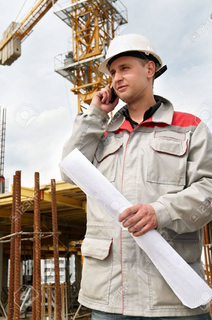 One happy engineer builder with blueprint at construction site speaking on mobile phone Stock Photo - 7398010