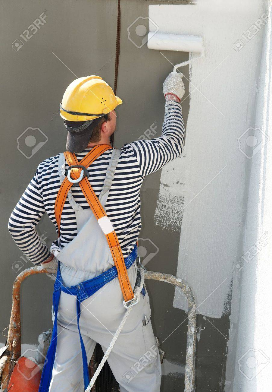 builder worker painting facade of high-rise building with roller Stock Photo - 7397845