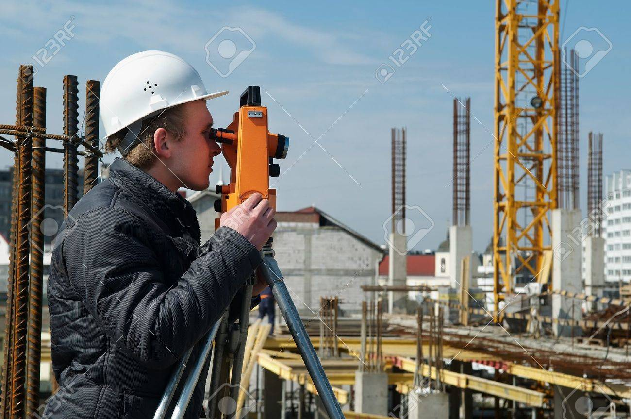 worker surveyor measuring distances, elevations and directions on construction site by theodolite level transit equipment Stock Photo - 7397836