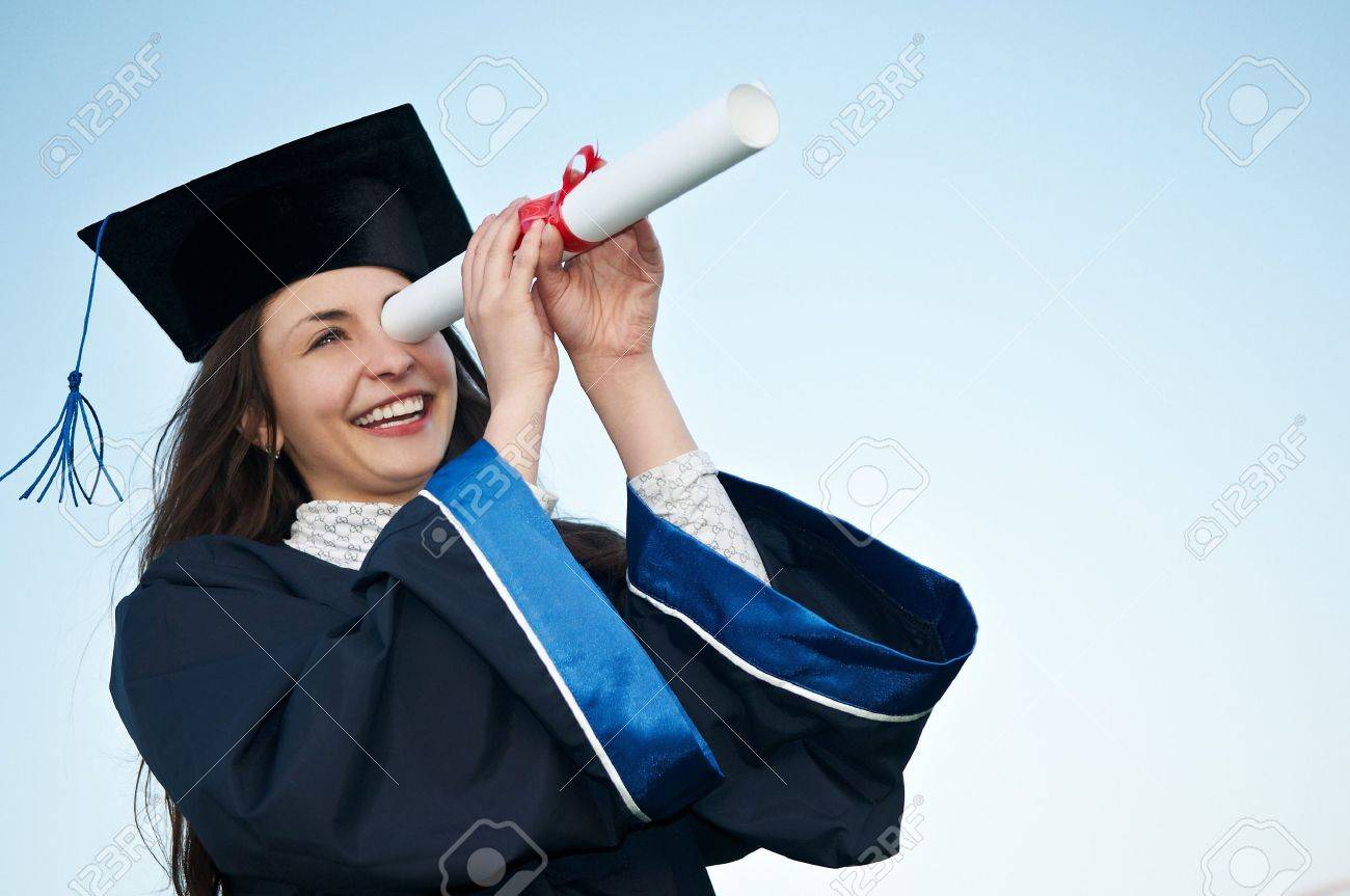 Young laughing graduate girl student in gown looking through diploma outdoors Stock Photo - 7399879