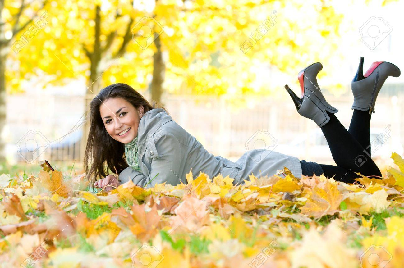 One young pretty student girl in yellow autumn leaves with computer laptop Stock Photo - 8207048