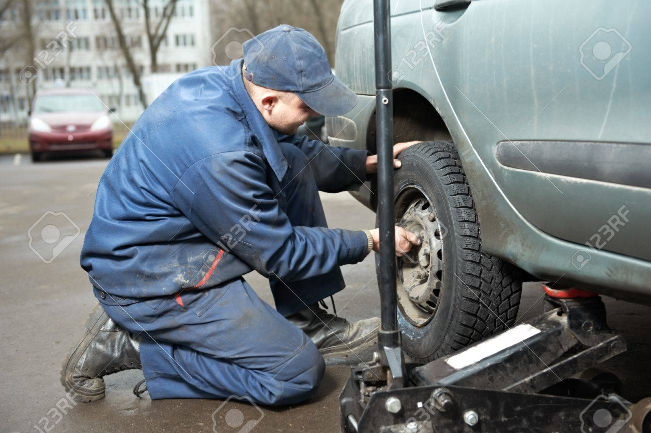 machanic repairman at tyre fitting with car jack Stock Photo - 11305133