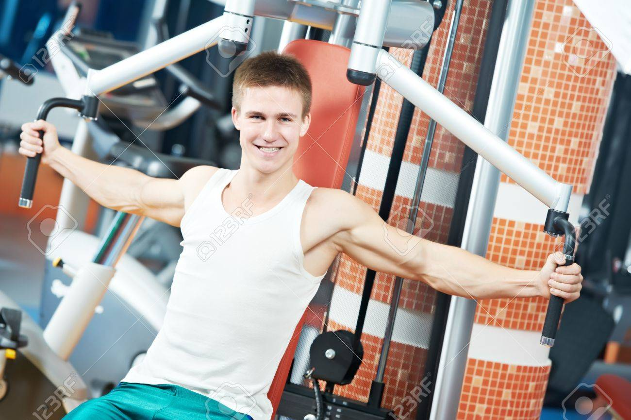 positive man at chest exercises machine Stock Photo - 11702028