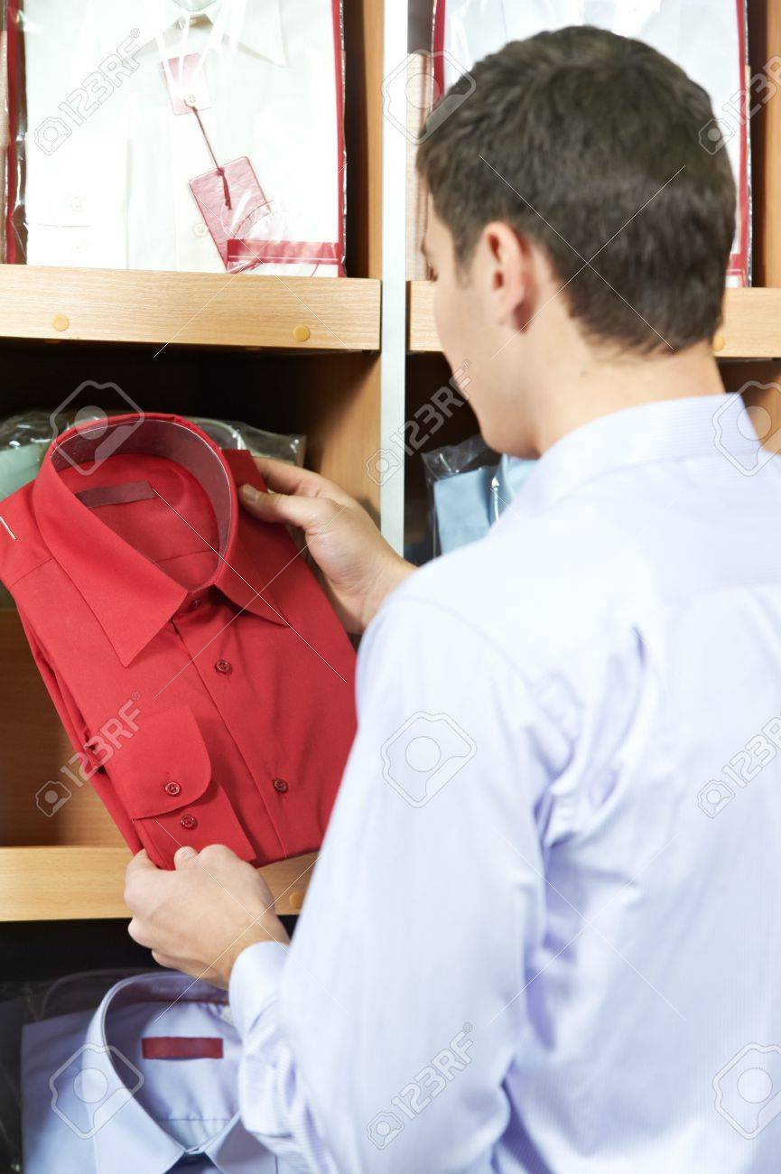 Young man choosing shirt in clothes store Stock Photo - 12589613