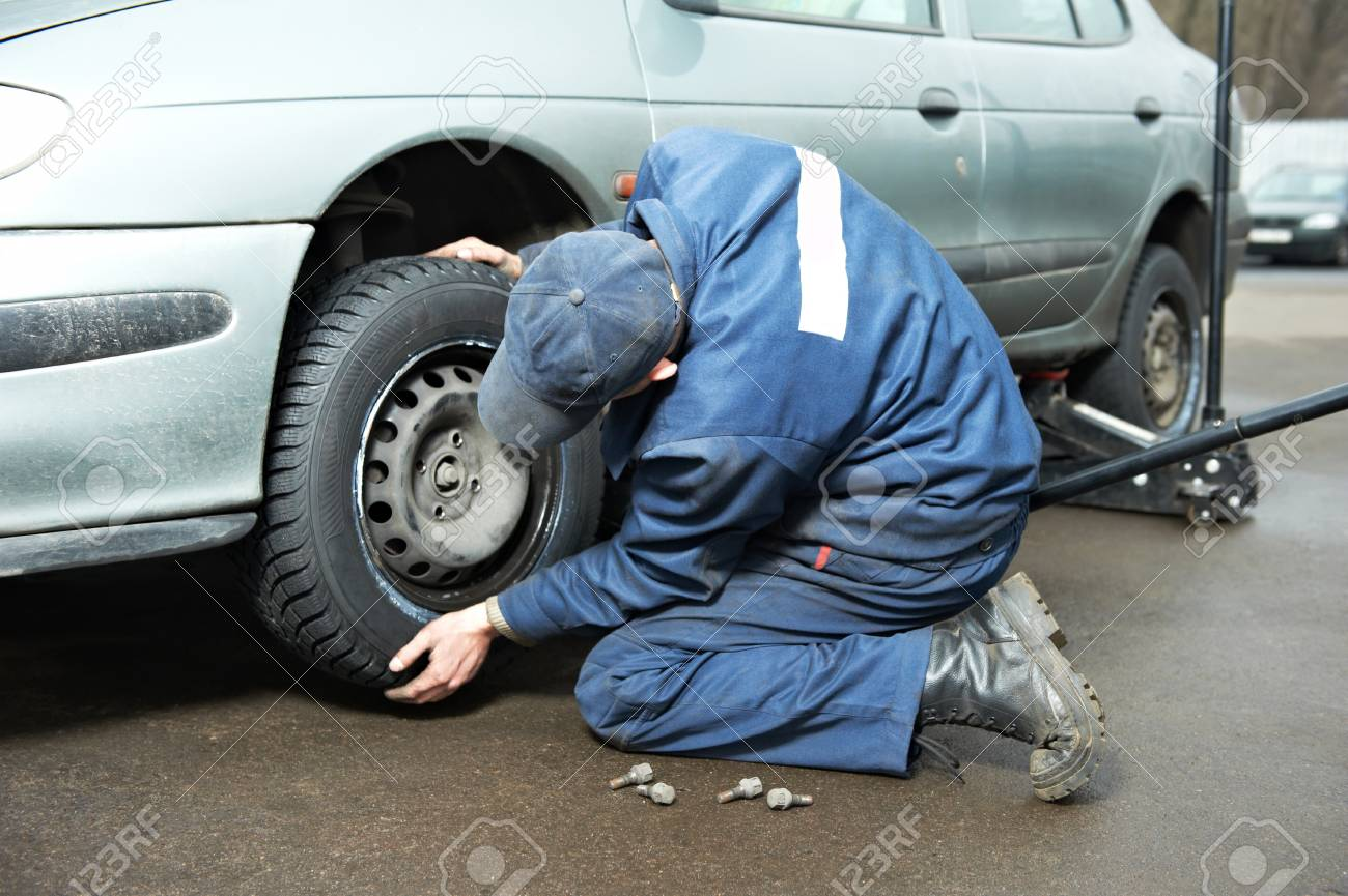 machanic repairman at tyre fitting with car jack Stock Photo - 12590237