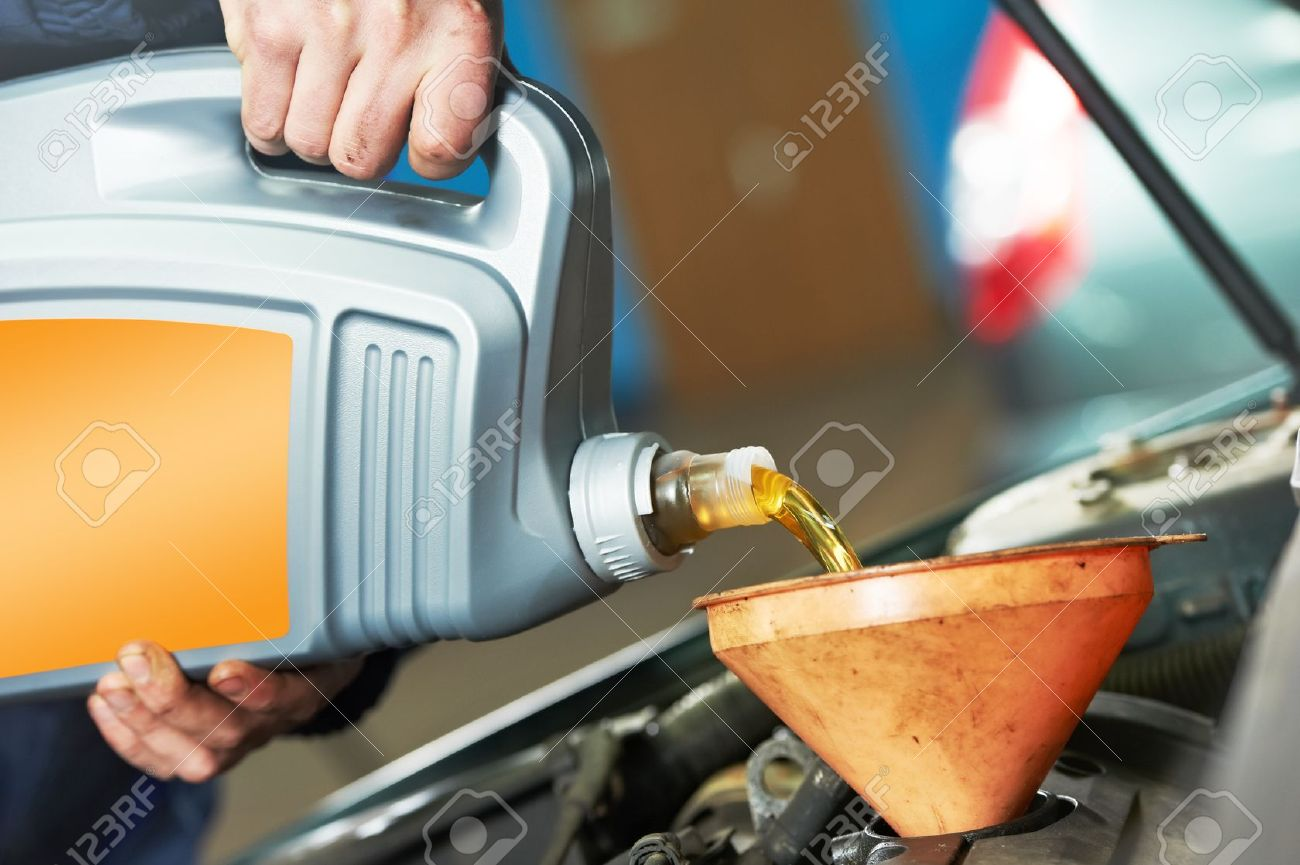 Engine oil closeup mechanic hand pouring oil into car motor stock photo