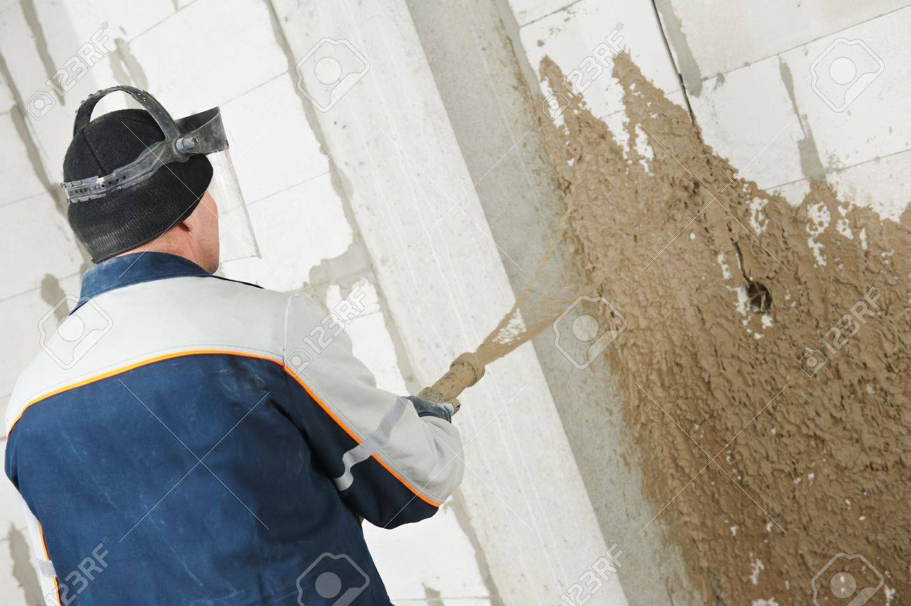 Plasterer at stucco work with liquid plaster - 13293584