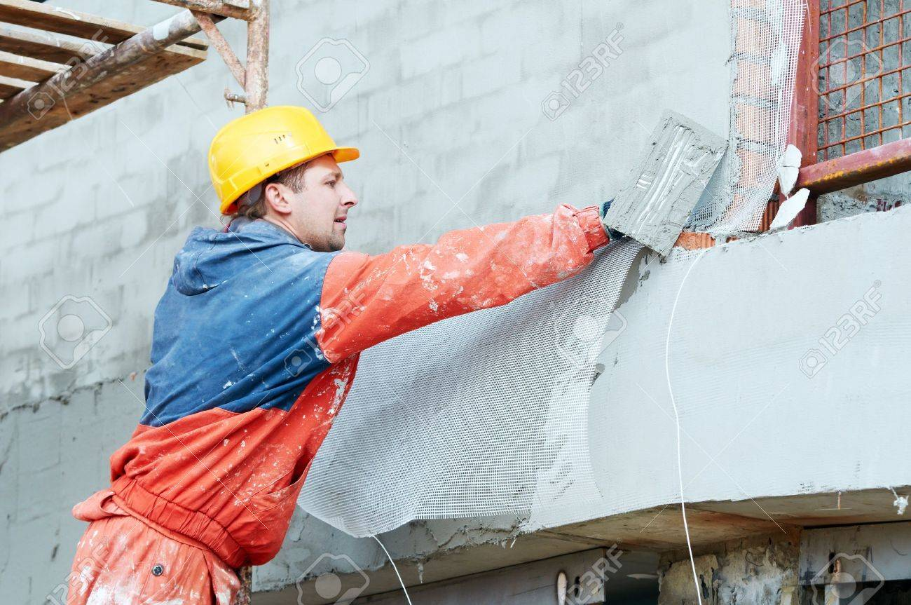 Builder at facade plastering works Stock Photo - 14051327