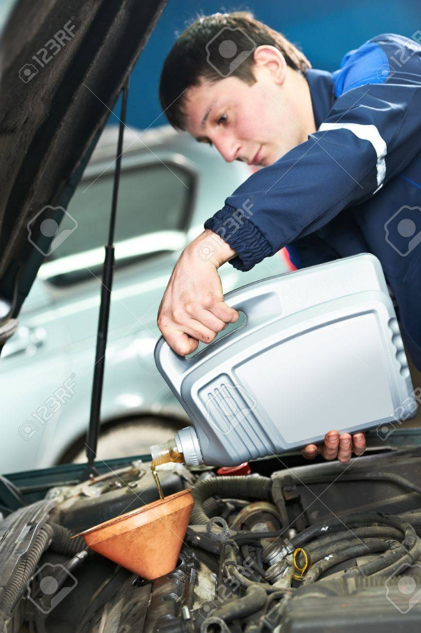auto mechanic technician replacing and pouring motor oil into automobile engine at maintenance repair service station Stock Photo - 21769525