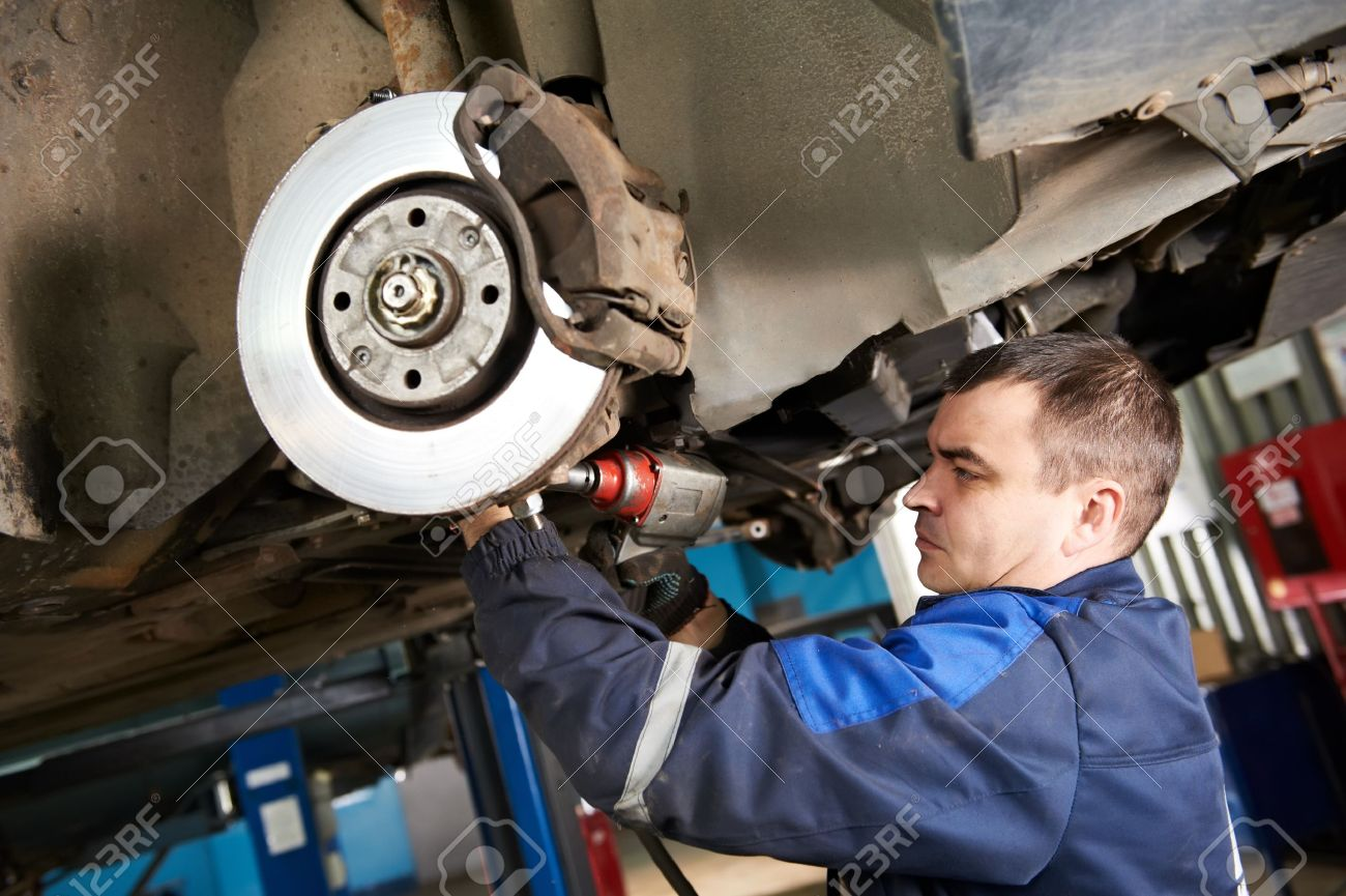 Car Mechanic Examining Car Suspension Of Lifted Automobile At ...