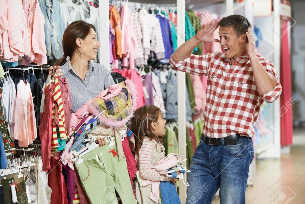 ab6cc2fbbbb Foto de archivo - Mujer y pequeñas tiendas de ropa niña