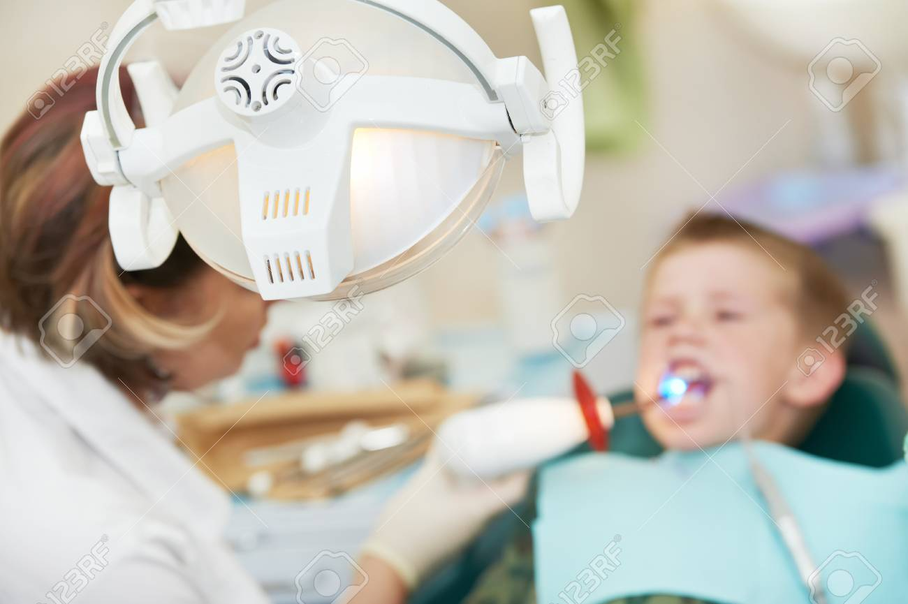 dental filing of child tooth by ultraviolet light Stock Photo - 18347376