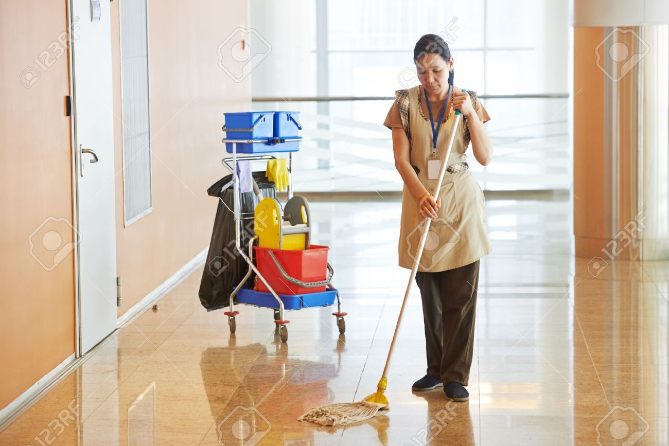 Female cleaner maid woman worker with mop in uniform cleaning corridor pass or hall floor of business building - 21769662
