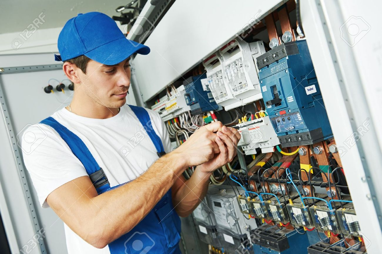 Young adult electrician builder engineer screwing equipment in fuse box - 21716825