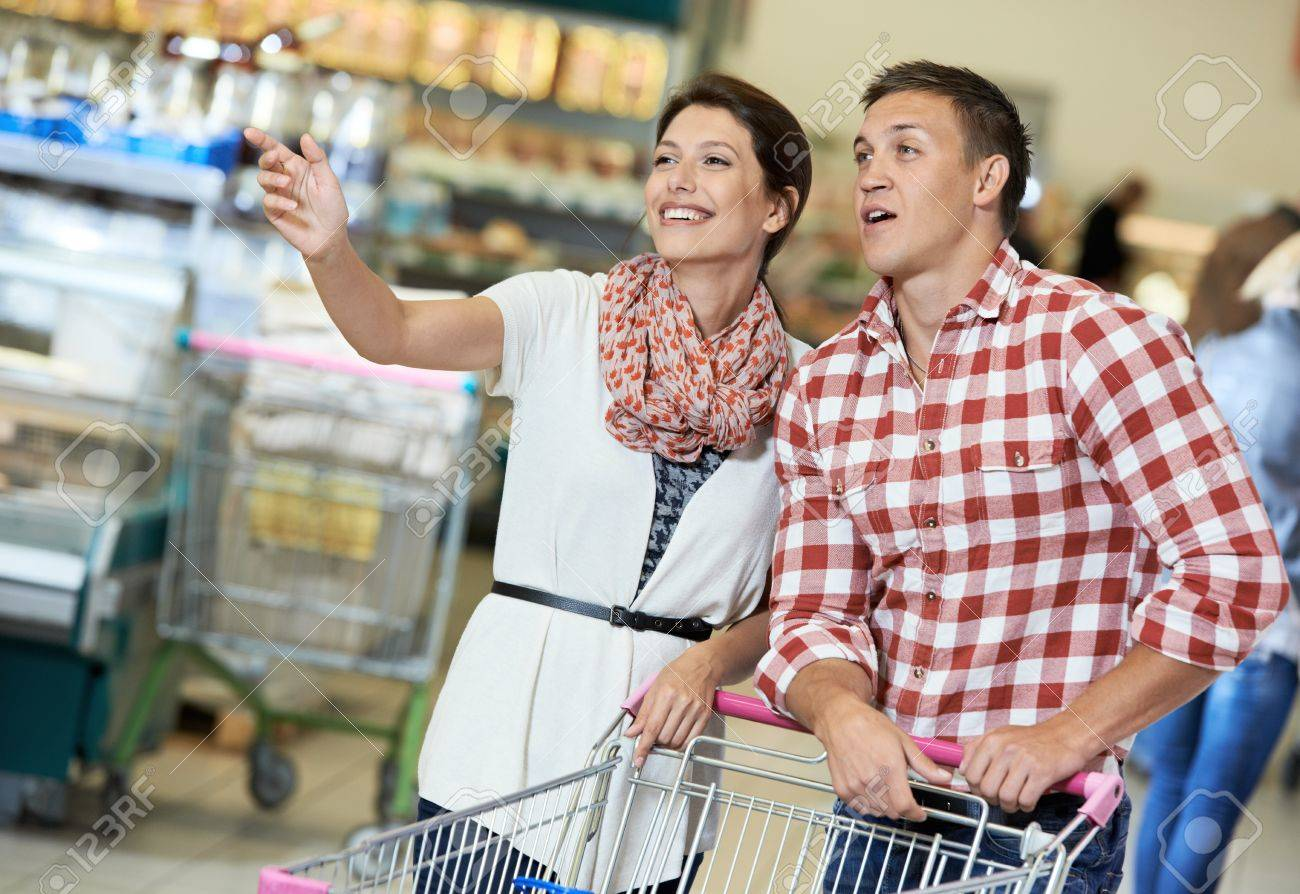 Family couple with trolley cart in meat grocery supermarket during weekly food shopping Stock Photo - 21810629
