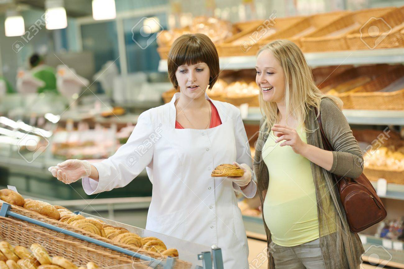 s assistant in supermarket demonstrating food to female s assistant in supermarket demonstrating food to female customer during shopping at store stock photo