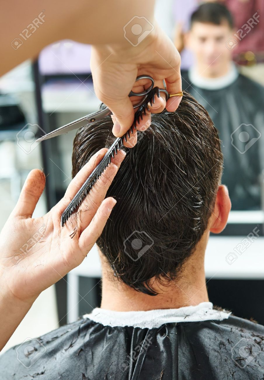 Hairdresser making haircut to young man at beauty parlour Stock Photo - 21946011