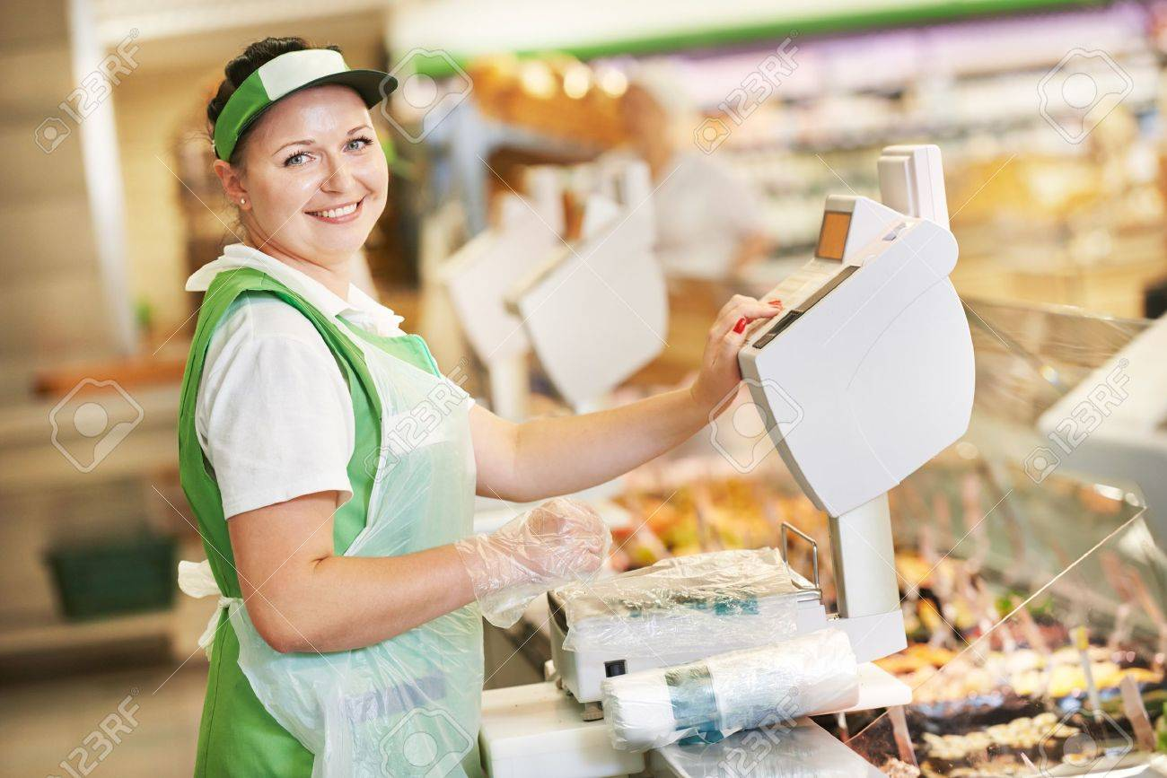 smiling sw assistant in supermarket working scales smiling sw assistant in supermarket working scales balance to pregnant female customer during shopping at