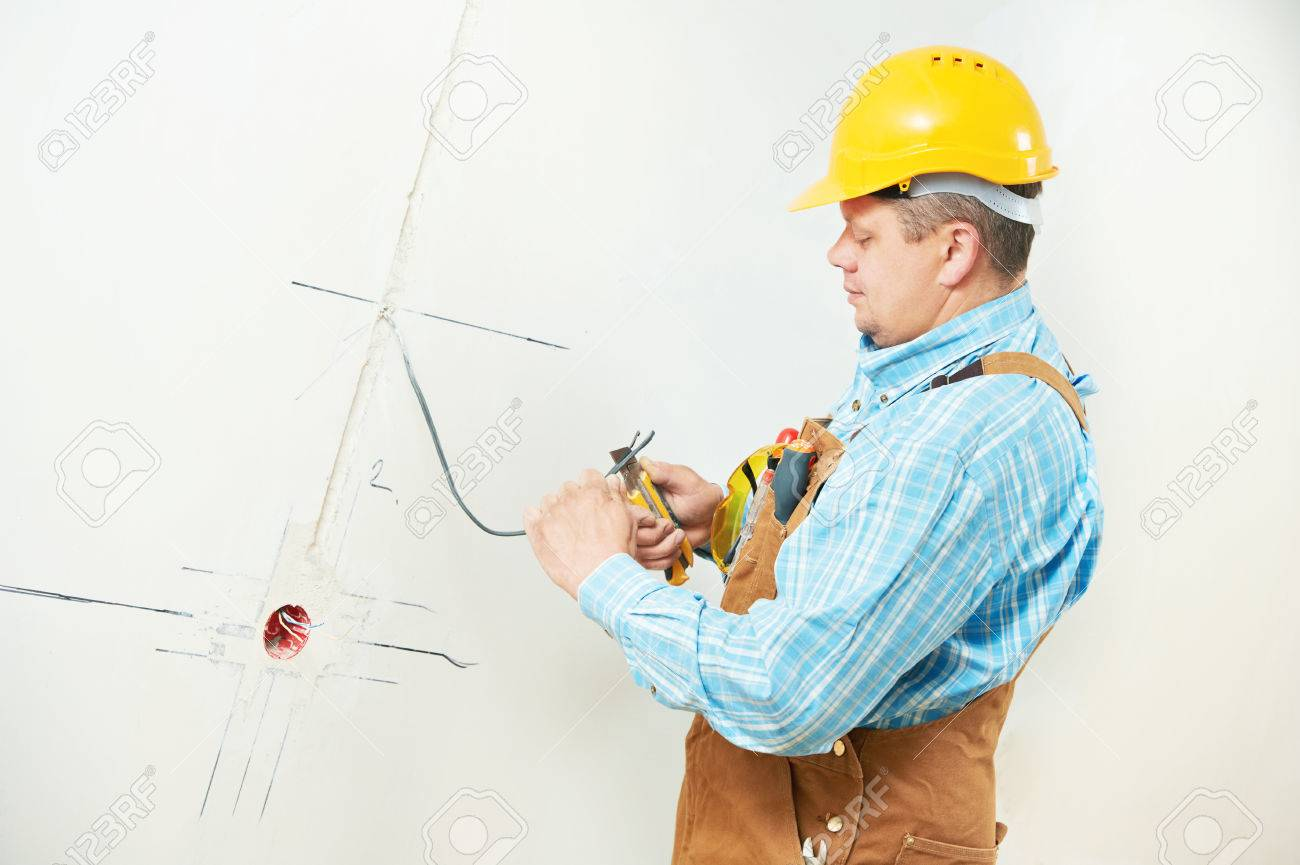 One Electrician Worker At Wiring Cable And Light Switch Or Power Socket Wall Outlet Installation Work