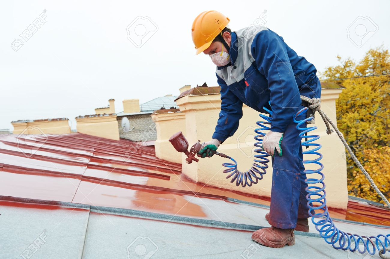 roofer builder worker with pulverizer spraying paint on metal