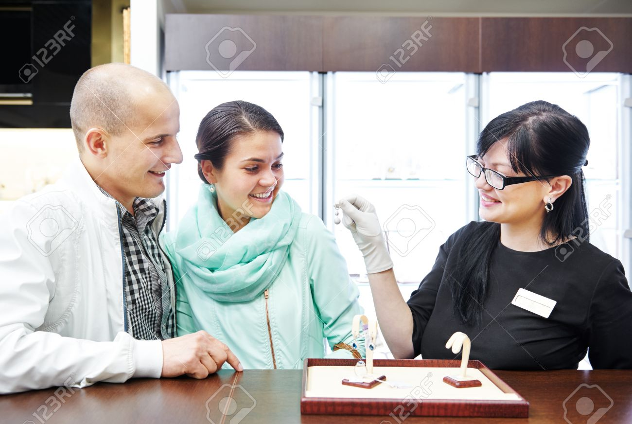 s assistant in jewelry shop demonstrating earring to young s assistant in jewelry shop demonstrating earring to young couple customers during gift selecting stock photo