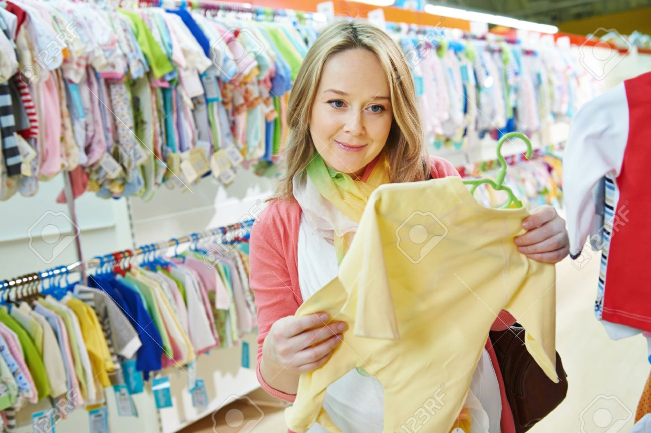4149c187e Young Pregnant Woman Choosing Newborn Clothes At Baby Shop Store ...