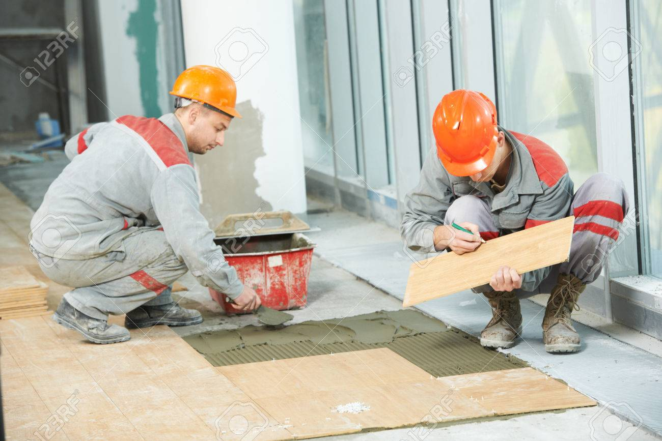 Two industrial tiler builder worker installing floor tile at two industrial tiler builder worker installing floor tile at repair renovation work stock photo 24711644 dailygadgetfo Images