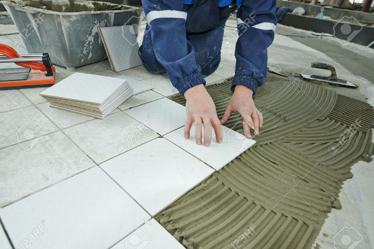 industrial tiler builder worker installing floor tile at repair