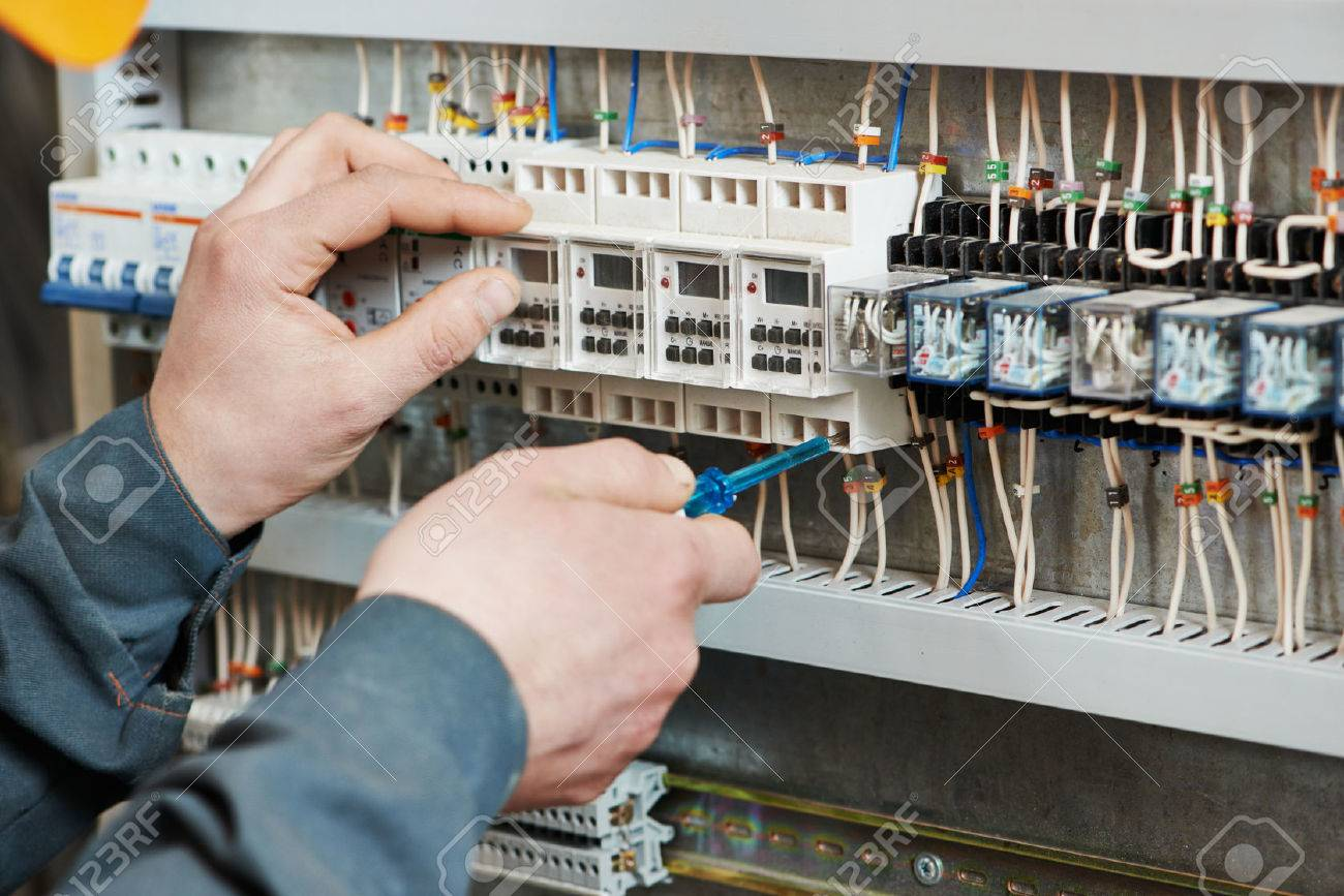 26774089 Hands of electrician with screwdriver tighten up switching electric actuator equipment in fuse box Stock Photo electric circuit breaker images & stock pictures royalty free converting fuse box to circuit breakers at virtualis.co