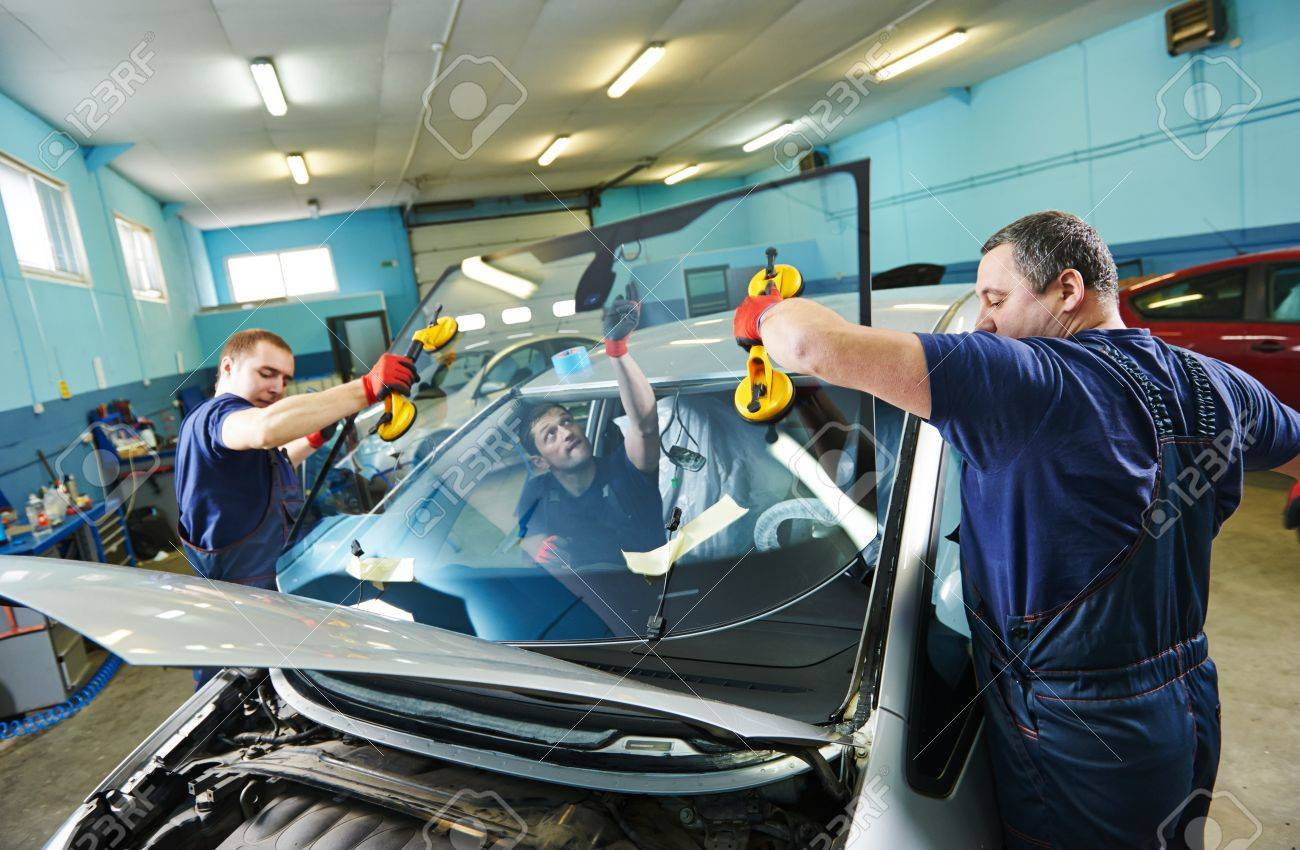 Automobile glaziers workers replacing windscreen or windshield of a car in auto service station garage Stock Photo - 27896507
