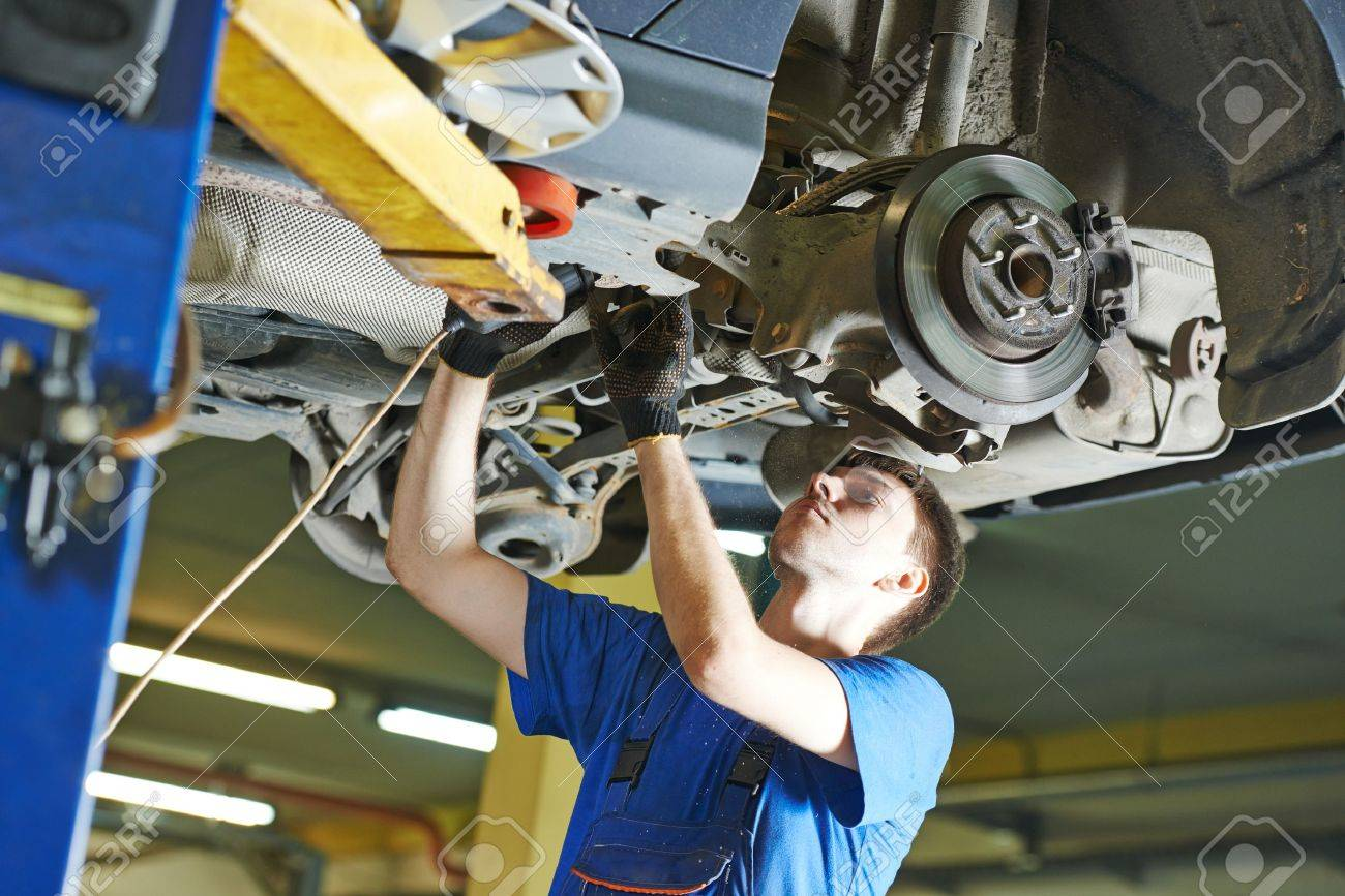 Garage Auto Mechanic Repairman Checking Car Suspension During