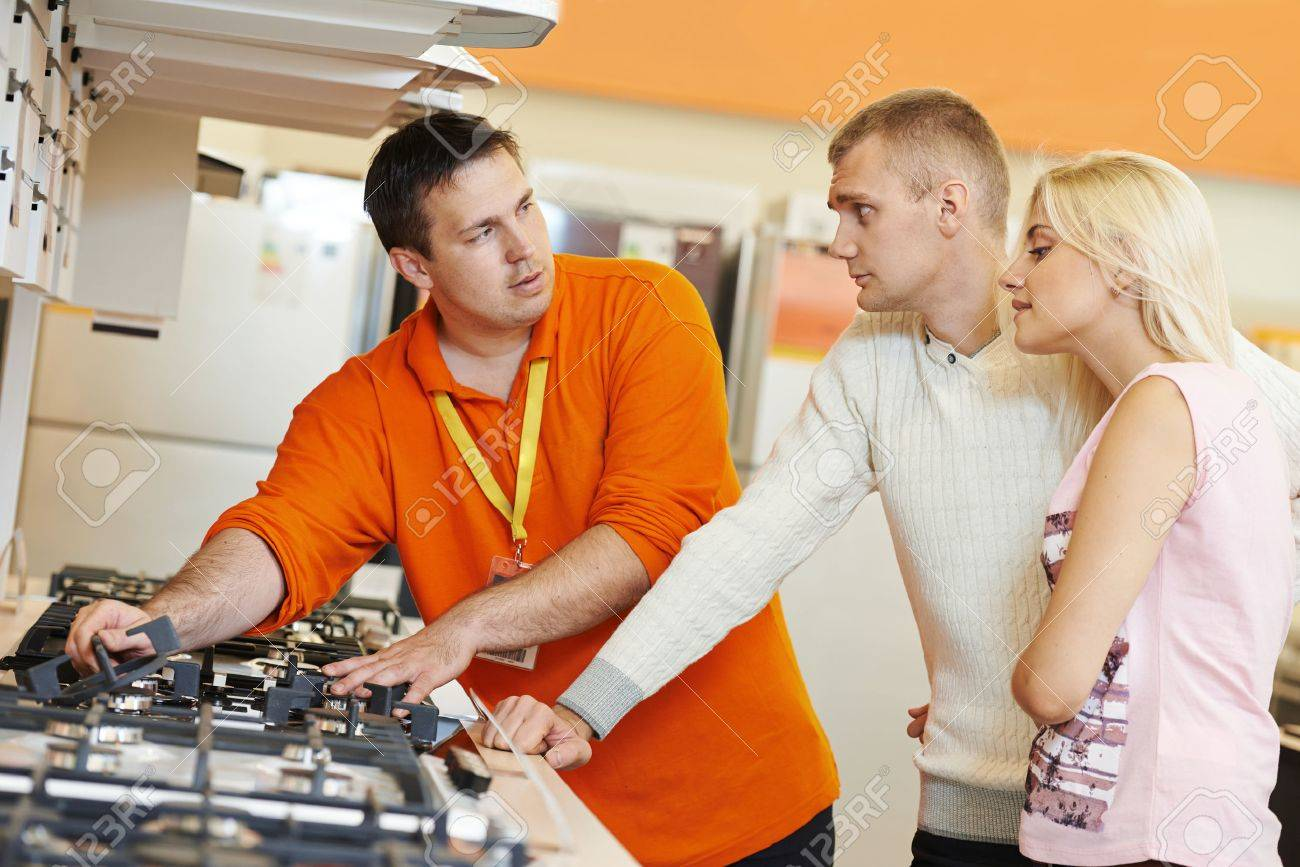 assistant demonstrating cooker stove to young family in assistant demonstrating cooker stove to young family in home appliance shopping mall supermarket stock photo