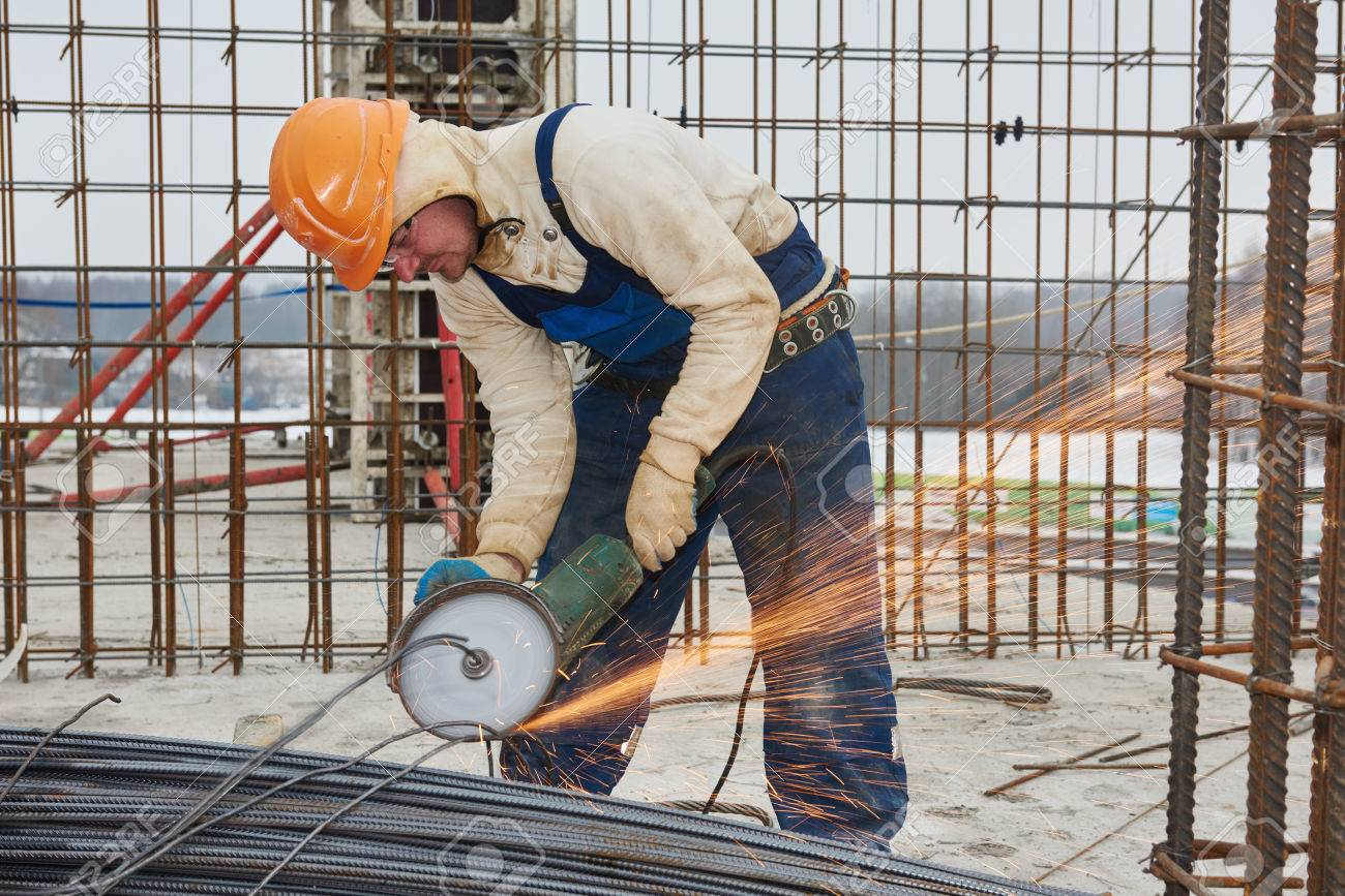 construction builder worker with grinder machine cutting metal reinforcement rebar rods at building site stock photo