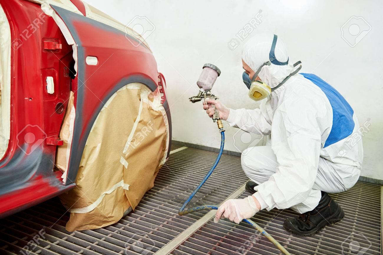 Mécanicien automobile travailleur peindre une voiture rouge dans une  chambre de peinture lors de travaux de réparation