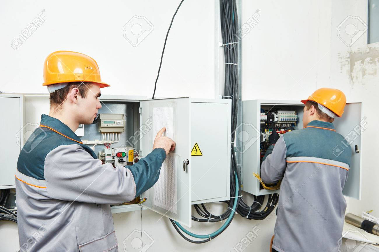 Two Electrician Builder Engineer Works With Electric Cable Wiring ...