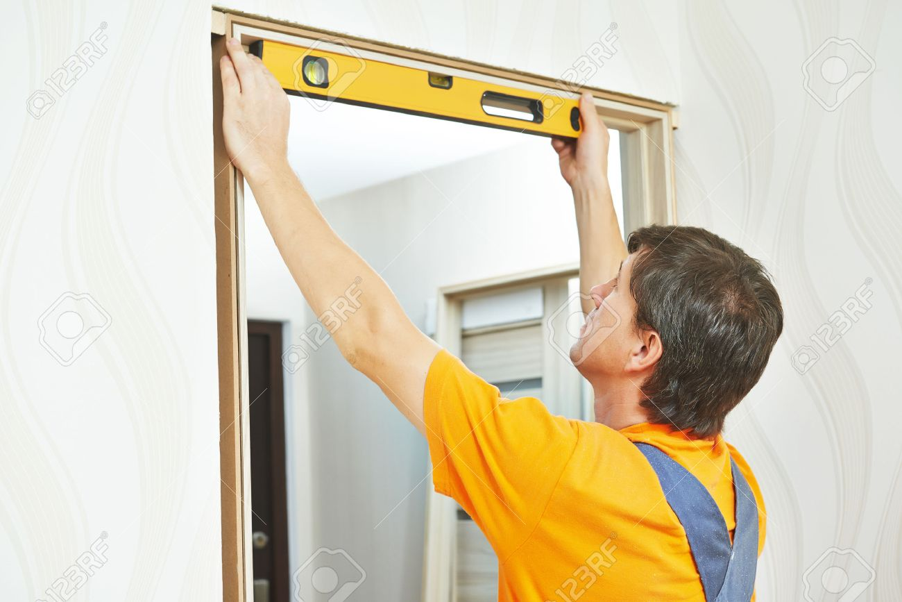 Male carpenter at interior wood door installation working with level Stock Photo - 37640199 & Male Carpenter At Interior Wood Door Installation Working With ... Pezcame.Com