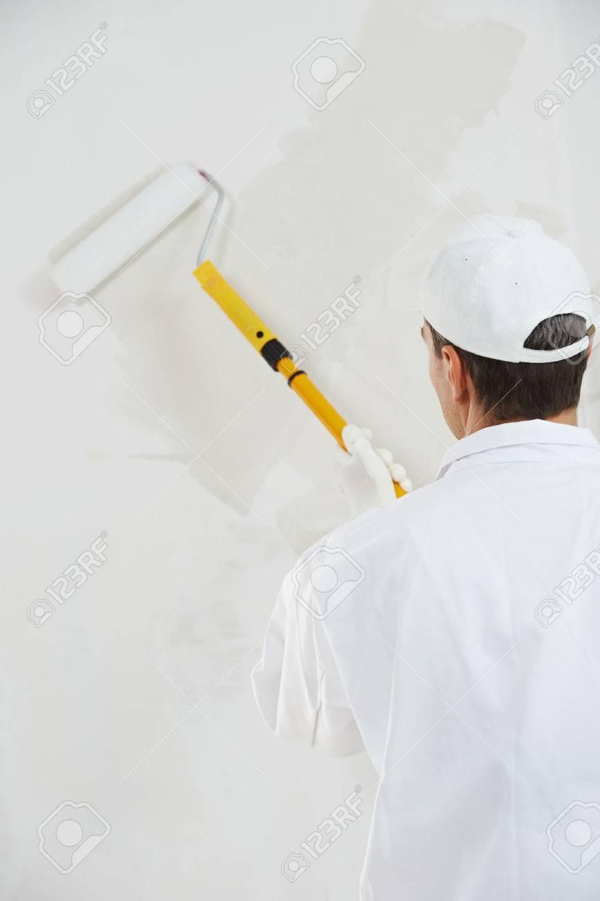 eine männliche anstreicher arbeiter malerei und grundierung wand mit