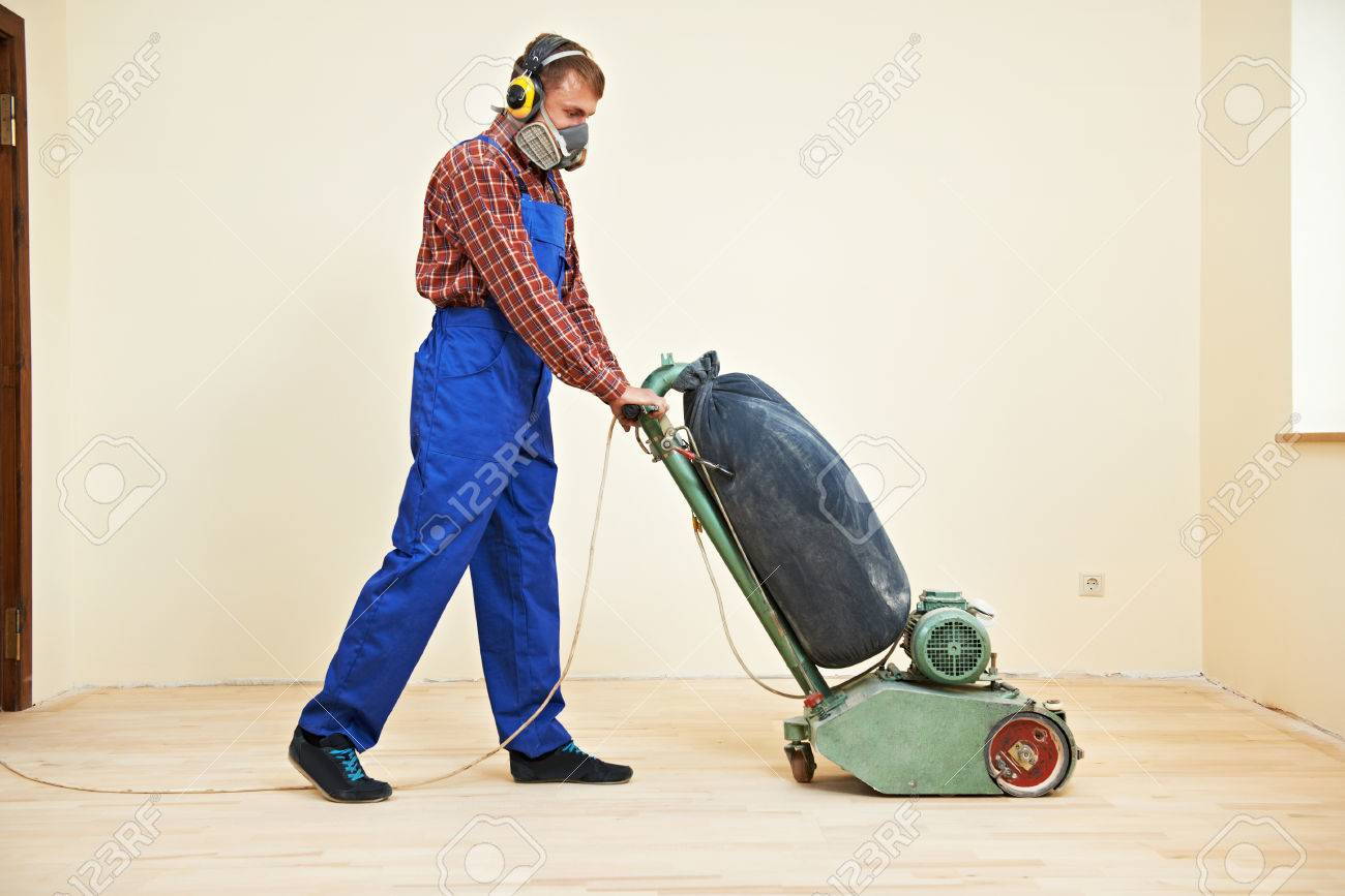 Stock Photo - carpenter doing parquet Wood Floor polishing maintenance work  by grinding machine - Carpenter Doing Parquet Wood Floor Polishing Maintenance Work