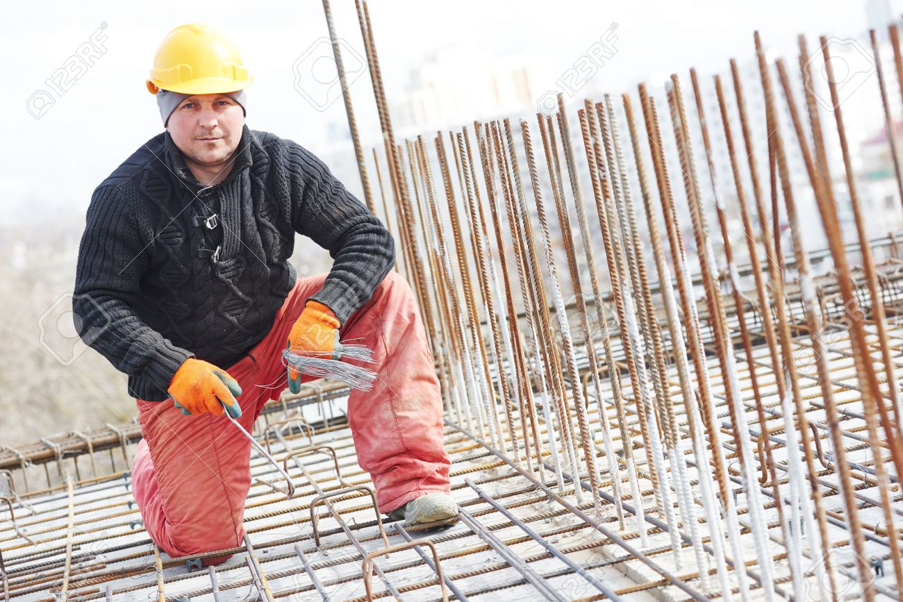 construction worker portrait during reinforcement work with metal rebar rods at building site stock photo